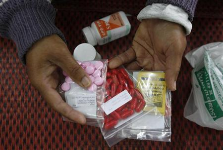 An HIV-infected patient displays medicine at a hospital in Payao province