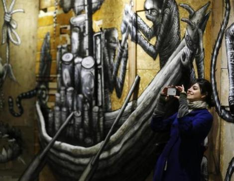 "A visitor photographs artist Phlegm's art installation ""The Bestiary"" at the Howard Griffith Gallery in London"