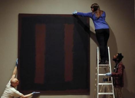 """Tate staff pose with the restored Mark Rothko artwork """"Black on Maroon, 1958"""" at the Tate Modern in London"""