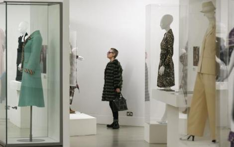 "A visitor looks at clothing on display in the ""Women Fashion Power exhibition at the Design Museum in London"