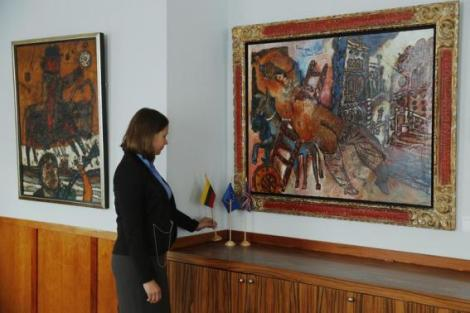 """Embassy intern poses with the artworks """"Man on a Bull"""" and """"Odalisque of the Grand Canal"""" by artist Theo Tobiasse at the Embassy of Lithuania in London"""