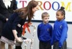 Britain's Kate, Duchess of Cambridge, receives a child's chair from Je'nane Edwards and Frankie Hudson at the Clore Art Room in west London