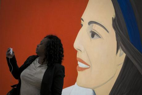 A woman takes a selfie photo with the 'Red Smile' by Alex Katz during the opening preview at The Whitney Museum of American Art in New York