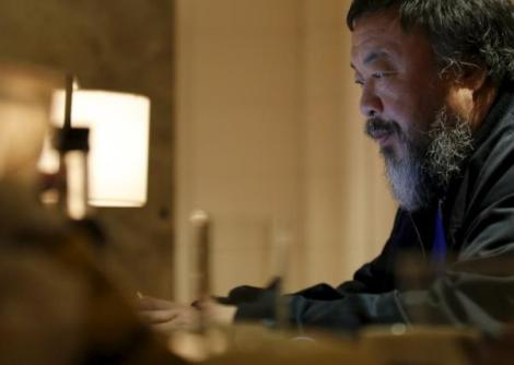 Dissident Chinese artist Ai Weiwei uses his laptop after an interview with Reuters at the hotel he is staying at in Beijing, March 24, 2015. REUTERS/Kim Kyung-Hoon