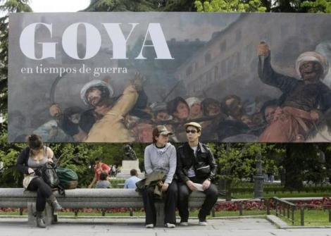 People sit in front of a banner announcing an exhibition by Spanish legendary artist Francisco Goya at Madrid's El Prado museum in Madrid April 15, 2008. REUTERS/Andrea Comas